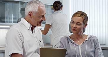Dr. Hansen während der Veneer-Beratung einer Patientin. / Dr. Rüdiger Hansen, Zahnarzt München
