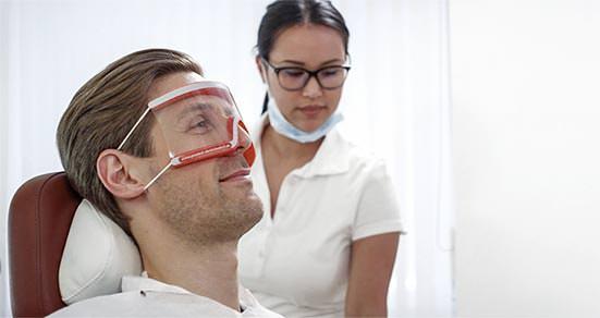 Patient und ZMA bei der Vorbereitung zur mikroskopischen Wurzelbehandlung. / Dr. Rüdiger Hansen, Zahnarzt München