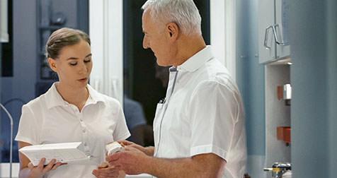 Dr. Hansen und ZFA während einer Besprechung. / Dr. Rüdiger Hansen, Zahnarzt München